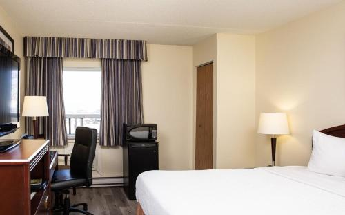 A bed or beds in a room at Travelodge by Wyndham Edmonton South
