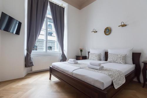 A bed or beds in a room at Barbo Palace Apartments and Rooms