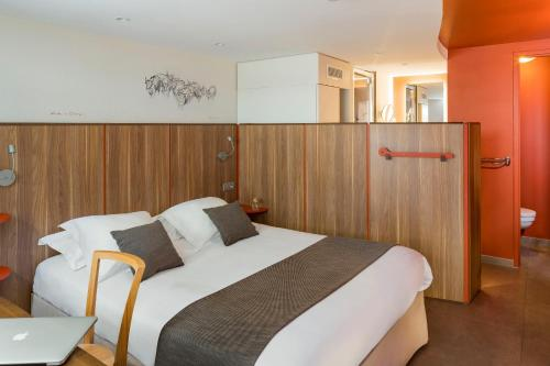 A bed or beds in a room at Terre de Provence Hôtel & Spa