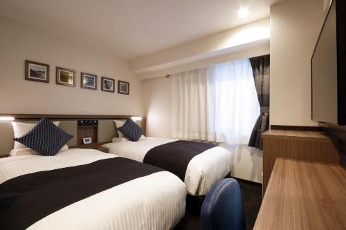A bed or beds in a room at HOTEL MYSTAYS Sapporo Susukino