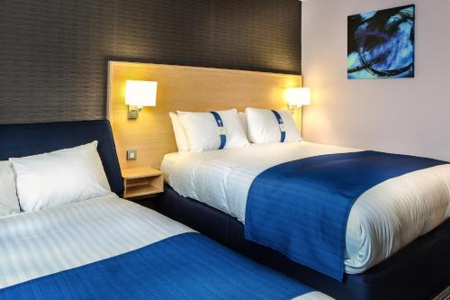 A bed or beds in a room at Holiday Inn Express Manchester Airport, an IHG Hotel