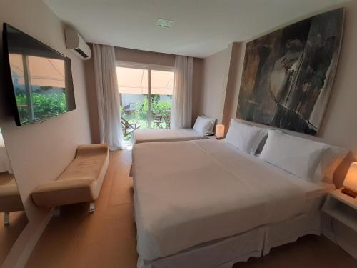 A bed or beds in a room at Parador Búzios Boutique Hotel