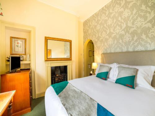 A bed or beds in a room at OYO Bailbrook Lodge