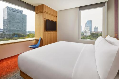 A bed or beds in a room at Aloft South Jakarta