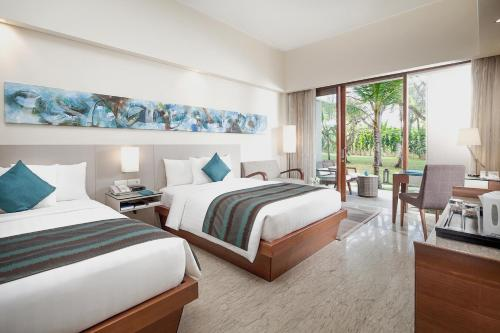 A bed or beds in a room at Courtyard by Marriott Bali Nusa Dua Resort