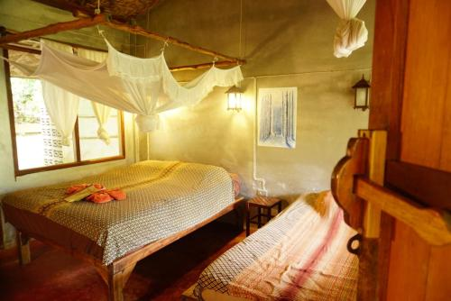 A bed or beds in a room at Eco-Logic, Resort for Charity