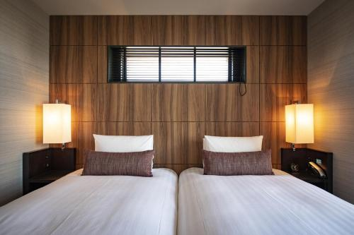 A bed or beds in a room at Solaria Nishitetsu Hotel Kagoshima