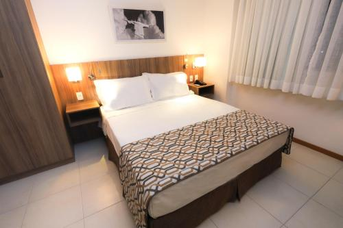 A bed or beds in a room at Promenade Soho Campos dos Goytacazes