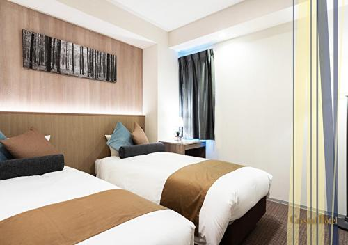A bed or beds in a room at Nippombashi Crystal Hotel Ⅱ
