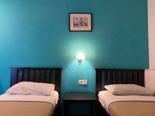 A bed or beds in a room at Old Penang Guesthouse
