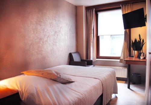 Een bed of bedden in een kamer bij Hotel Rubens