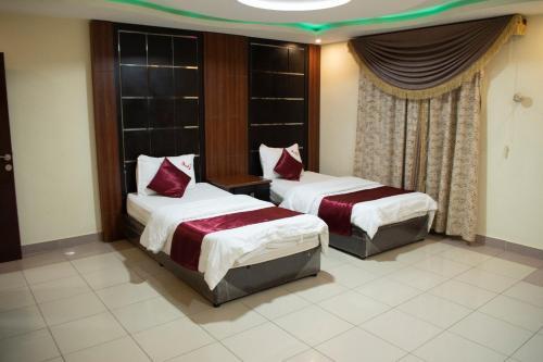Cama ou camas em um quarto em Rawasi rand Aparthotel