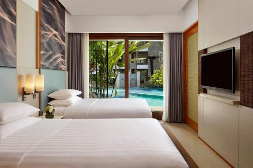 A bed or beds in a room at Courtyard by Marriott Bali Seminyak Resort