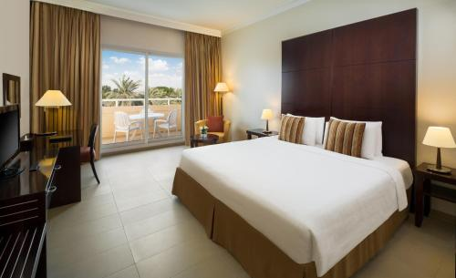 A bed or beds in a room at Millennium Central Al Mafraq