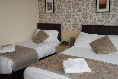 A bed or beds in a room at The Auckland Hotel