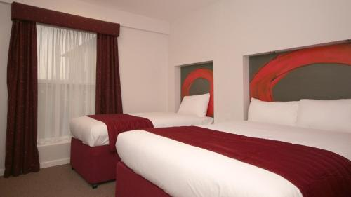 A bed or beds in a room at Ramada London Stansted Airport