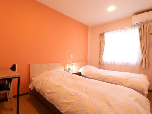 A bed or beds in a room at Hotel Asahi Grandeur Fuchu