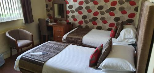 A bed or beds in a room at Best Western Grimsby Oaklands Hall Hotel