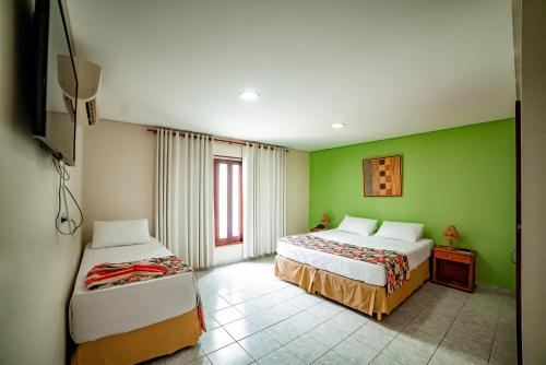 A bed or beds in a room at Hotel Três Palmeiras
