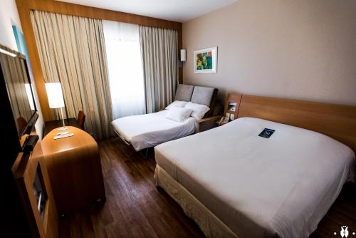 A bed or beds in a room at Novotel Porto Alegre Tres Figueiras