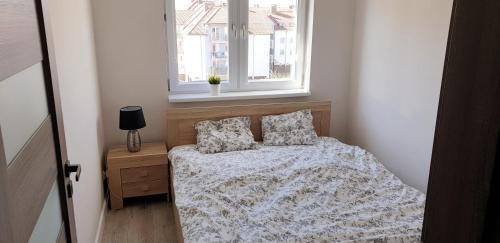 A bed or beds in a room at Apartament Młynarska