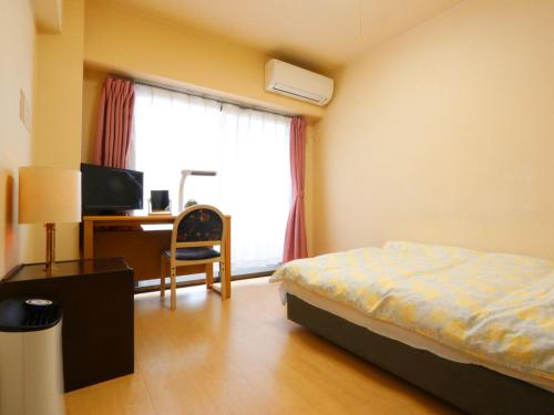 A bed or beds in a room at Business Inn Grandeur Fuchu