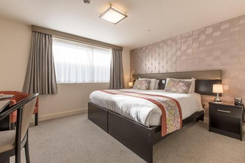 A bed or beds in a room at Mannin Hotel