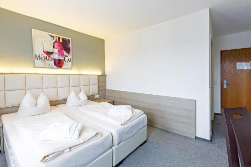 A bed or beds in a room at Bavaria Hotel Münchner Hof Superior
