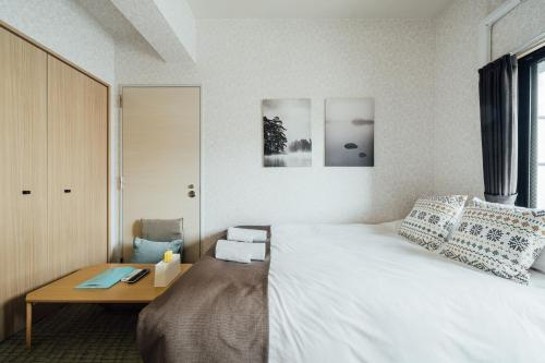 A bed or beds in a room at ALZA Fukushima AFP Apartment