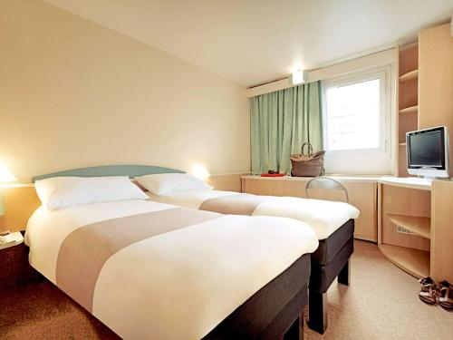 A bed or beds in a room at ibis Duisburg Hauptbahnhof