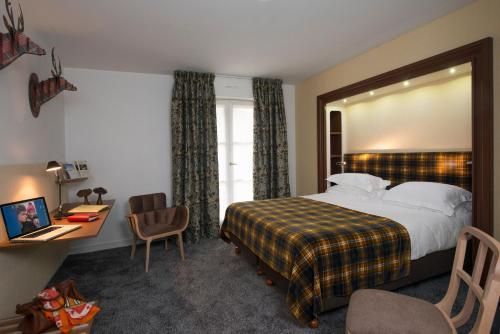 A bed or beds in a room at Le Manoir du Lys, The Originals Relais (Relais du Silence)