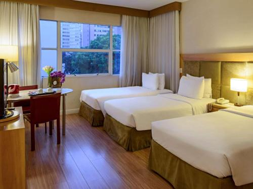 A bed or beds in a room at Mercure Sao Paulo Jardins