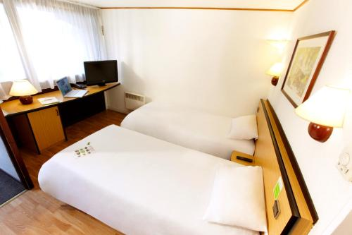 A bed or beds in a room at Campanile Rennes Atalante