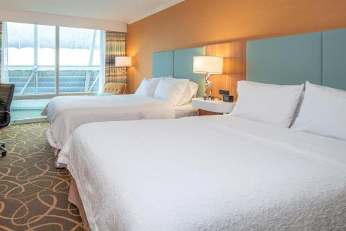 A bed or beds in a room at Hampton Inn & Suites, by Hilton - Vancouver Downtown