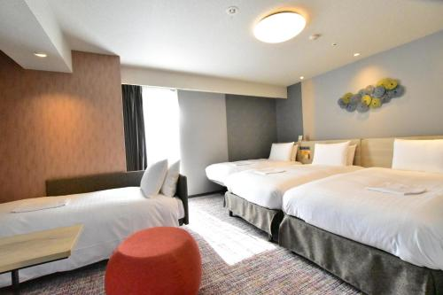 A bed or beds in a room at Richmond Hotel Akita Ekimae