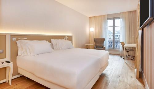 A bed or beds in a room at NH Collection Marseille
