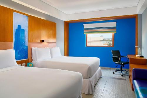 A bed or beds in a room at Aloft Cancun