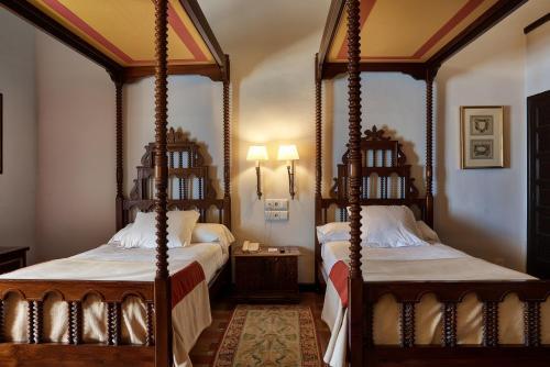 A bed or beds in a room at Parador de Ubeda