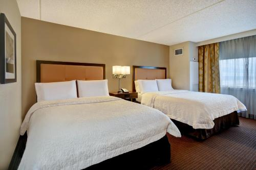 A bed or beds in a room at Hampton Inn NY-JFK