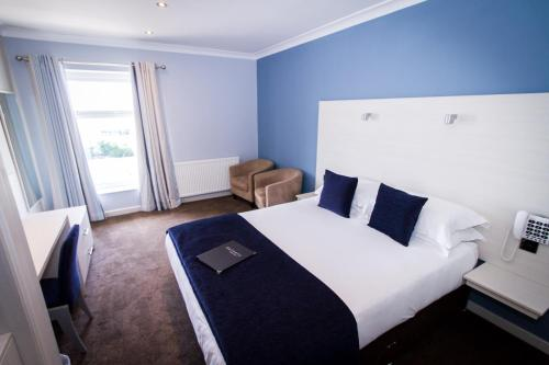 A bed or beds in a room at Dalmeny Hotel