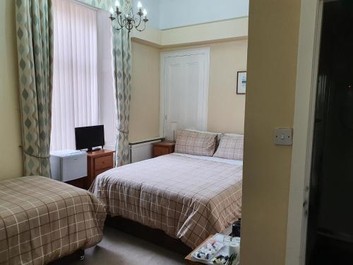 A bed or beds in a room at Dean Park Guest House