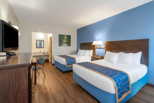 A bed or beds in a room at Days Inn by Wyndham Grants