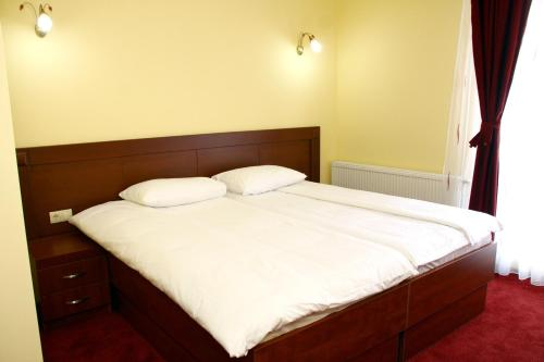 A bed or beds in a room at Hotel Parlament
