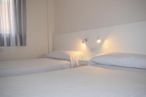 A bed or beds in a room at Apartamentos VIDA Corcubión