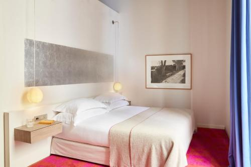 A bed or beds in a room at Hotel Neri – Relais & Chateaux