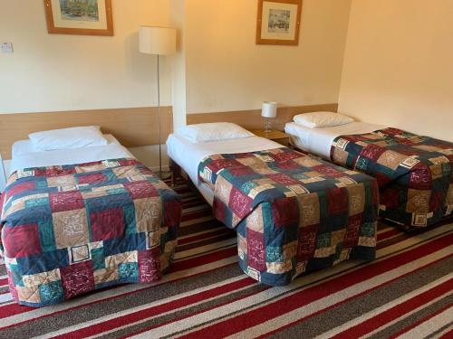 A bed or beds in a room at Strathpeffer Hotel