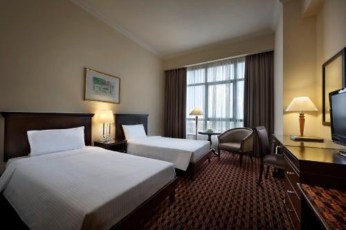A bed or beds in a room at Berjaya Penang Hotel