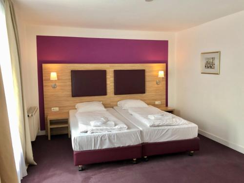 A bed or beds in a room at Park Hotel Theater Mönchengladbach