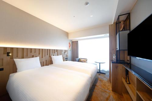 A bed or beds in a room at Miyako City Osaka Hommachi