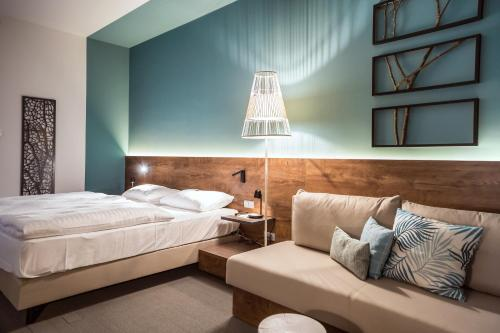 A bed or beds in a room at Das Sonnreich - Thermenhotel Loipersdorf
